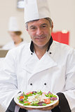 Smiling chef showing his salad