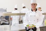 Smiling chef  showing her salad