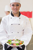 Cheerful chef showing her salad