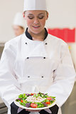 Cheerful chef looking at her salad
