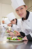 Smiling chef preparing salad in culinary class