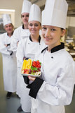 Smiling chef holding fruit plate