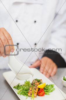 Chef pouring sauce on salmon