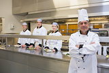 Head chef standing with team behind him