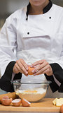 Chef cracking egg into bowl of flour