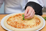 Basil leaf being put on pizza