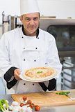 Cheerful chef presenting pizza