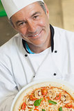 Smiling chef holding a pizza