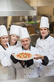Four Chef's holding a pizza