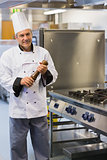 Smiling chef holding a pepper mill
