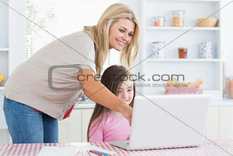 Mother pointing at laptop with daughter