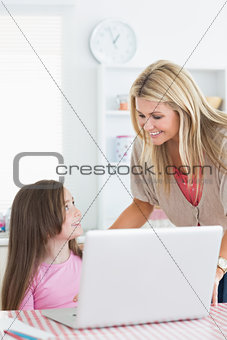 Woman and child smiling at each other in kitchen