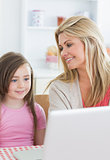 Mother smiling at daughter using laptop