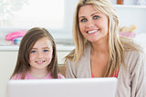 Woman and child sitting and smiling with laptop