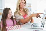 Mother pointing something out on laptop for daughter