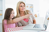 Child pointing something out on laptop to mother