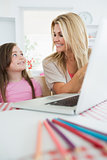 Woman smiling at her daughter by the laptop