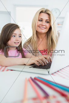 Mother watching child typing