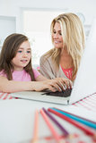 Little girl typing with mother smiling