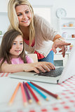 Mother pointing at laptop with daughter sitting down