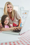 Little girl typing with mother watching at laptop
