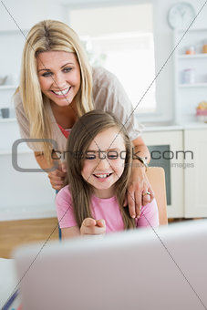 Little girl pointing at laptop and laughing with mother
