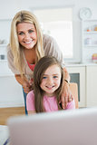Woman and daughter smiling at the laptop