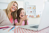 Woman and child sitting at the kitchen table laughing