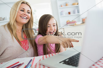 Little girl and mother laughing at laptop
