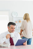 Man sitting at the kitchen with tablet pc and coffee