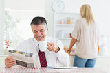 Man smiling while reading newspaper before work