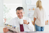 Man sitting at the kitchen table while holding a cup of coffee before work