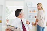 Couple laughing together in kitchen before work