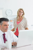 Wife looking upset at husband using laptop in kitchen