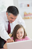 Father pointing at something on daughter's laptop and smiling