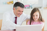 Man and girl sitting at the kitchen with laptop
