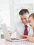 Man sitting with his daughter at the kitchen at laptop