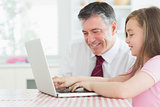 Girl typing with father watching