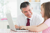 Man and daughter sitting at the kitchen at laptop