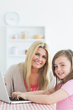 Woman and daughter sitting at the kitchen while smiling with a laptop