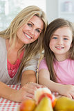 Mother and child sitting at kitchen table smiling
