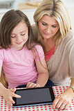 Child using tablet pc with mother in kitchen