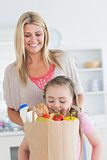 Daughter looking into grocery bag with mother watching