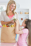 Woman giving green pepper to daughter from grocery bag