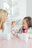Girl feeding her mum cereal