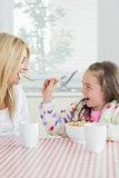 Girl feeding her mum cereal