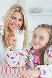 Mother and girl holding up glasses of milk