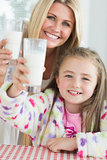Mother and daughter raising milk glasses