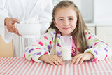 Happy little girl with glass of milk getting cereal from her mother