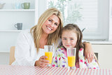 Woman and little girl sitting at the kitchen having juice